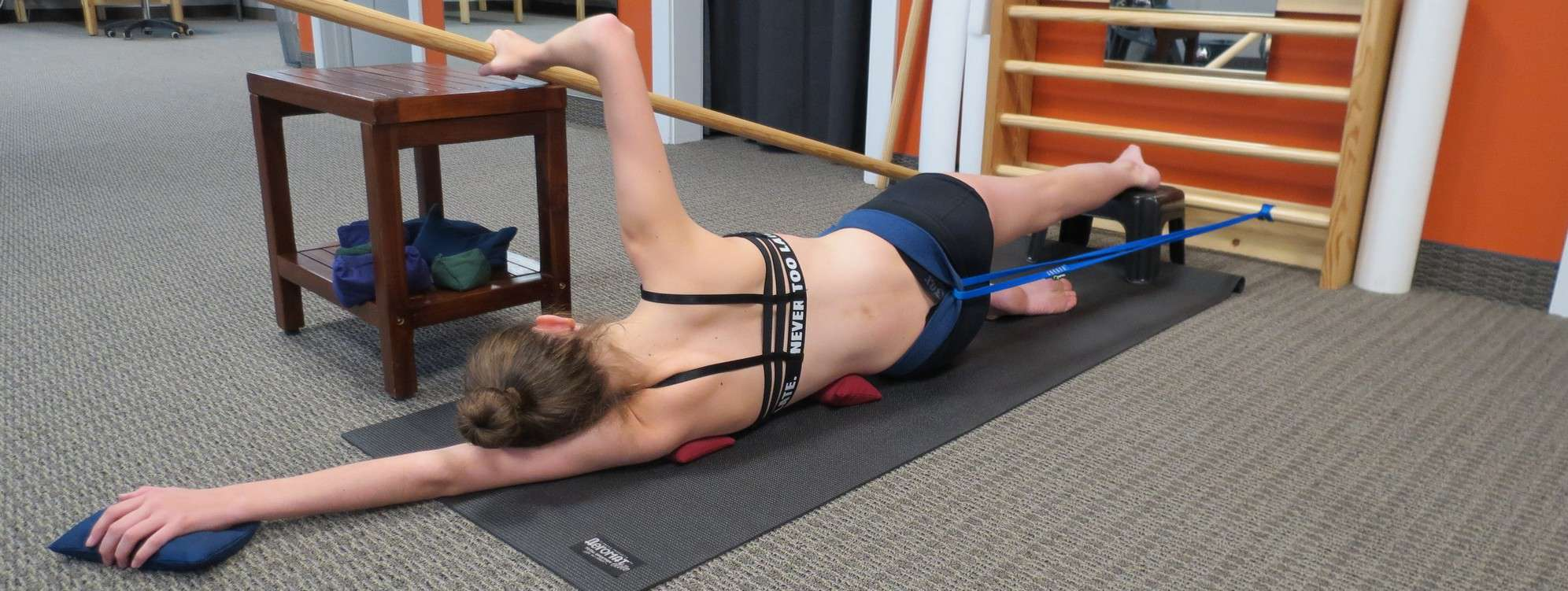 Schroth Method sidelying corrections lying on a yoga mat while holding a pole